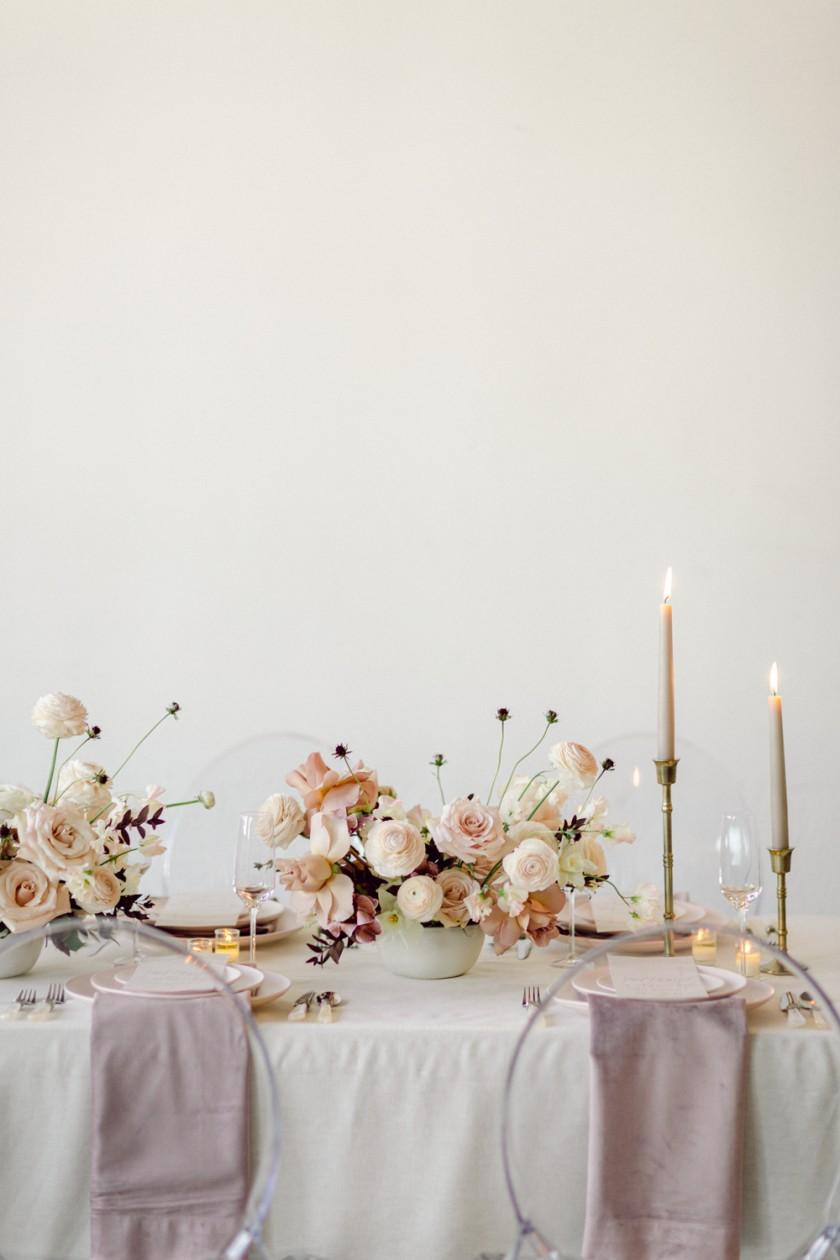 Delicate wedding table setting with flowers and details in pale lavender and blush colors.